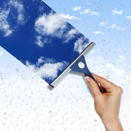 Hand cleaning window with blue sky and white clouds Stock Photo - 11988838