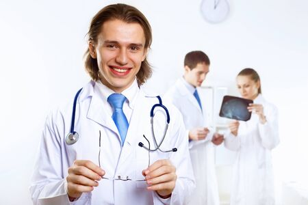 Young confident and friendly doctor in medical office photo