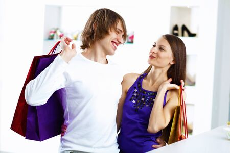 Young caucausian couple with bags doing shopping together photo