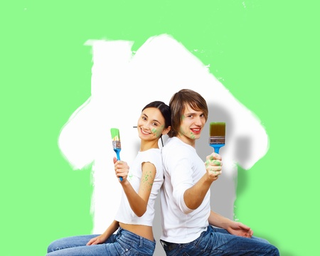 Young caucausian couple with paint brushes together photo