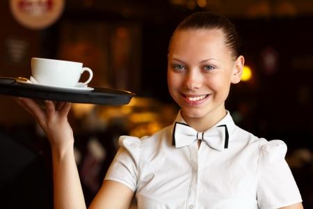 meseros: Retrato de joven camarera en la blusa blanca que sostiene una bandeja