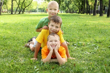 Group of children lying on the grass in the summer park photo