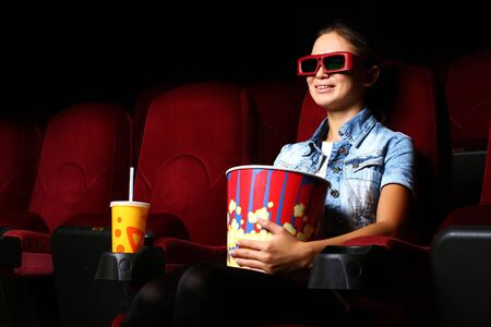 One young girl watching movie in cinema photo