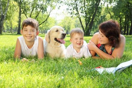 mamans: M�re et ses deux fils dans le parc avec un chien golden retriever