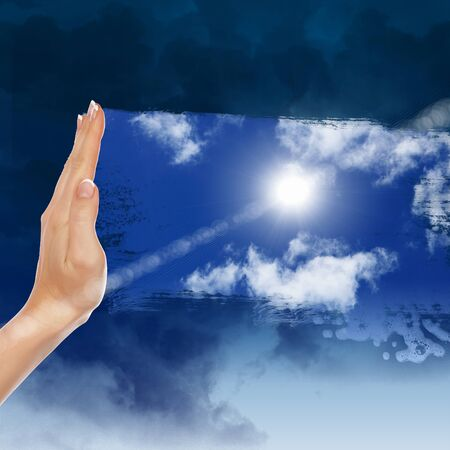 Hand cleaning window with blue sky and white clouds photo