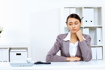 people waiting: Young woman in business wear sitting with a phone in office