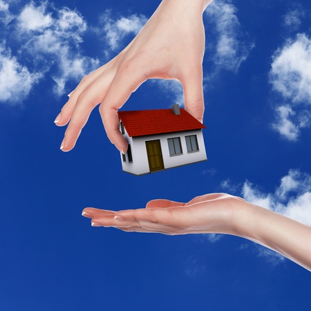 Human hand against blue sky background and house Stock Photo - 12404006