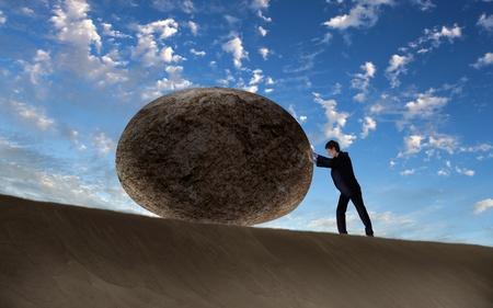 empujando: Imagen del empresario rodar una piedra gigante Foto de archivo