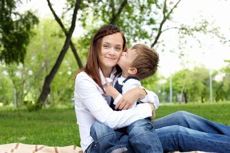 madre e hijo: Madre con su hijo sentado y abrazando en el parque de verano Foto de archivo