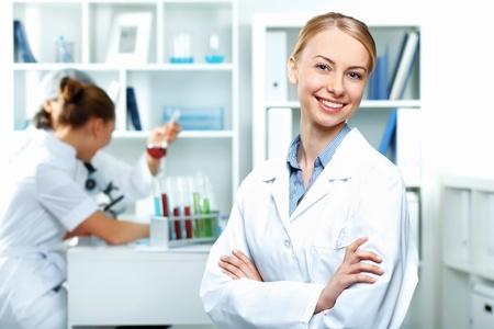 Los científicos jóvenes en uniforme blanco que trabajan en el laboratorio