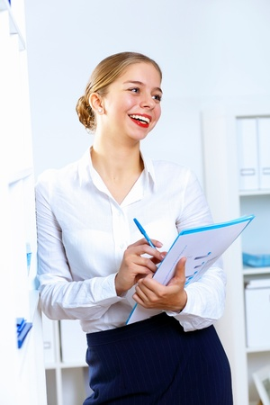 Young pretty woman in business wear working in office photo