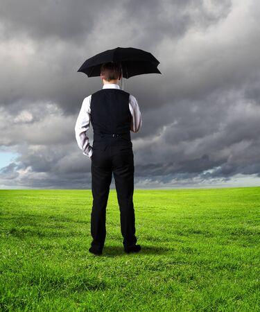 lluvia paraguas: Collage con joven hombre de negocios contra el fondo del tiempo Foto de archivo