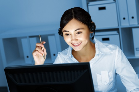 Young woman in business wear in headset working with computer Stock Photo - 12404264