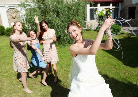 Young bride in white wedding dress throws a bouquet of flowers to bridesmaids photo