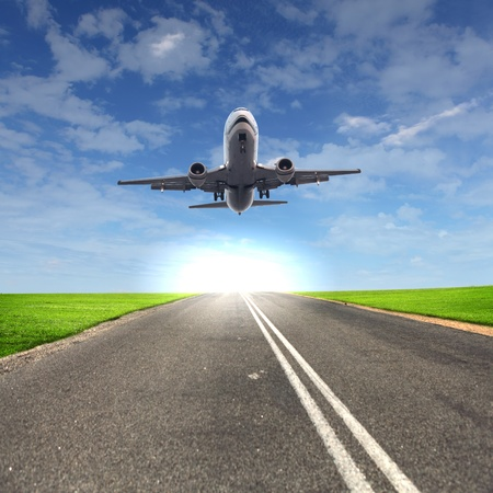 plane landing: Image of a white passenger plane and blue sky with clouds