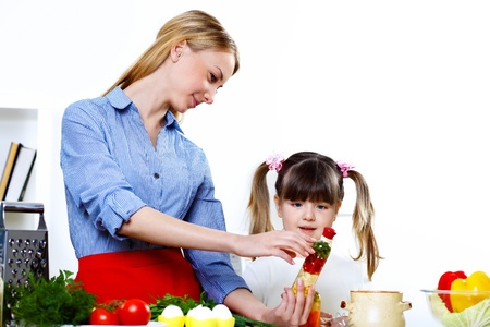 Young mother cooking fresh meal at home with her daoghter photo
