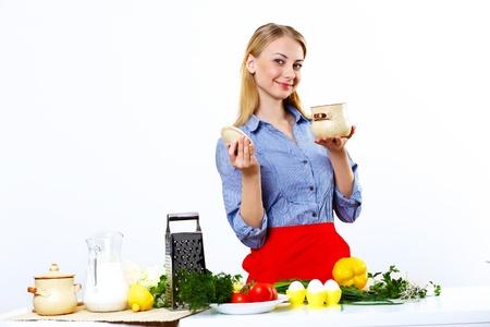 jasschort: Jonge gelukkige vrouw koken verse maaltijd thuis Stockfoto