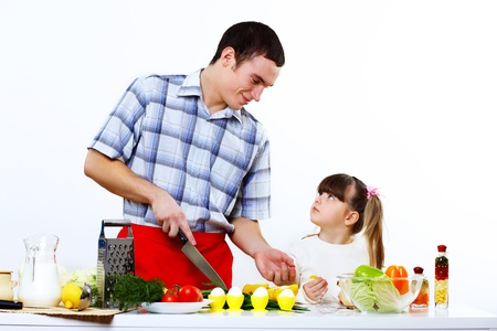 Happy young family with a daughter cooking together at home photo