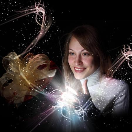 Jeune femme d'ouvrir une boîte cadeau avec aveuglante et scintillante et lumières autour de sa