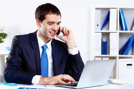 telephone salesman: Young smiling happy businessman at work in office