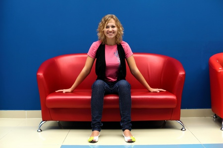 red sofa: Portrait of young woman sitting on red sofa against blue wall