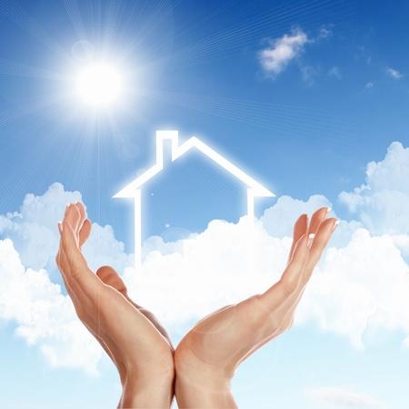 Mano umana contro il cielo blu e la casa