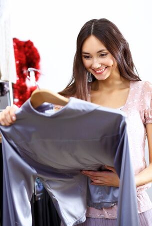 clothing store: Portrait of young woman inside a store buying clothes