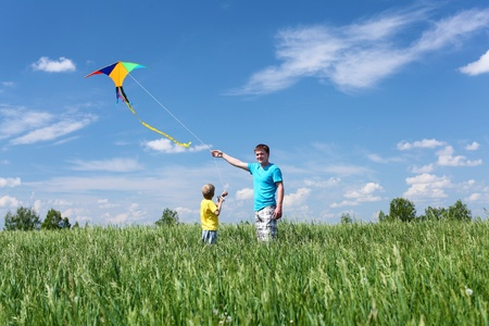 father with son in summer playing with kite photo