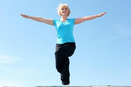 Portrait of a senior woman doing yoga outdoors photo
