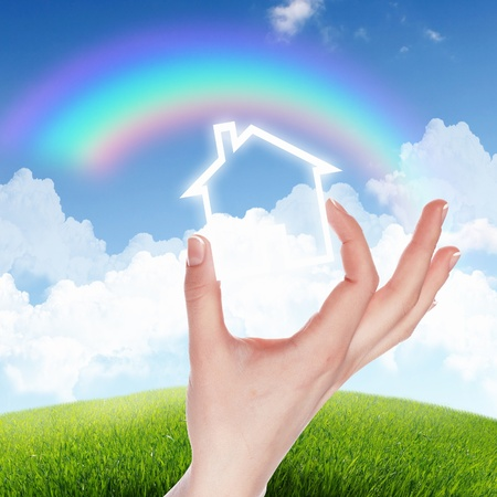Human hand against blue sky background and house photo
