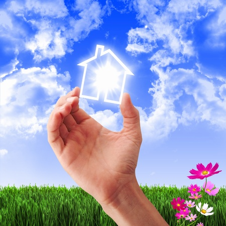 Human hand against blue sky background and house Stock Photo - 12561488