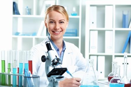 investigador cientifico: Joven cient�fico con el uniforme blanco de trabajo en el laboratorio