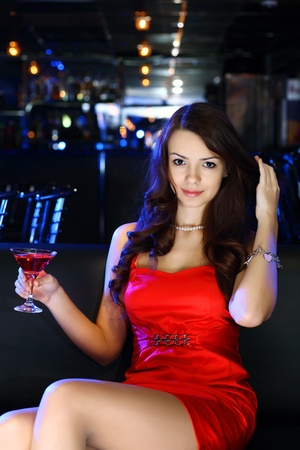 Portrait of young attractive woman in night club with a drink Stock Photo - 12561359