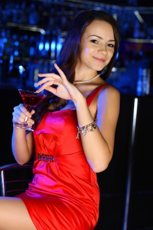 Ritratto di giovane donna attraente in night club con un drink photo