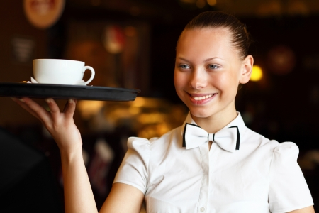 Portrait of young waitress in white blouse holding a tray Stock Photo - 12561431