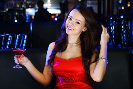 Portrait of young attractive woman in night club with a drink Stock Photo - 12561364