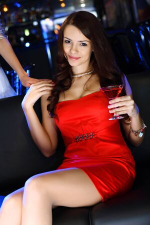 Portrait of young attractive woman in night club with a drink Stock Photo - 12561379