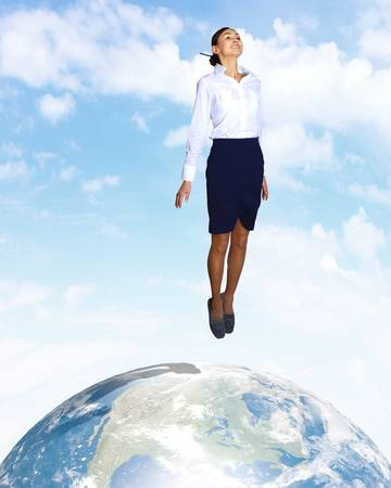 Young woman jumping up with our planet earth below photo