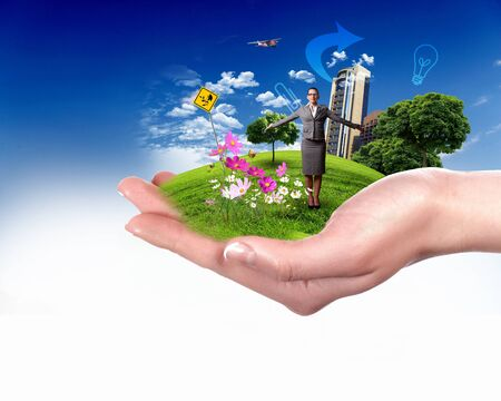 Collage with a human hand holding a green landscape photo