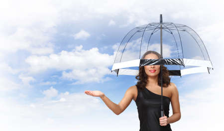 Young pretty woman with umbrella against sky background photo