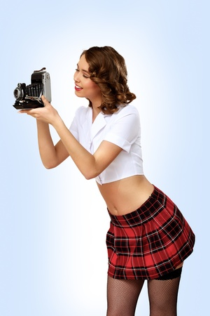 Studio portrait of a woman dressed in retro style with camera photo