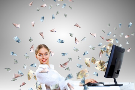 a lot of money: Young businesswoman in the office with money banknotes around her Stock Photo