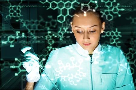 examenes de laboratorio: Joven qu�mico con el uniforme blanco de trabajo en el laboratorio