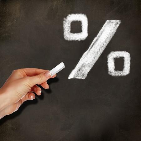 School blackboard and hand with chalk writing percentage symbol on it photo