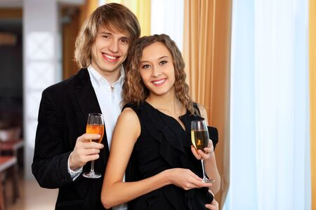Young handsome man and pretty woman in a restaurant with shampagne photo