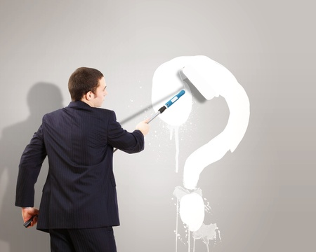 Businessman with paint brash and picture of question mark on the wall photo
