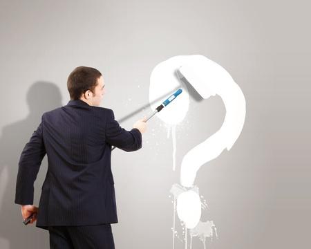 onbeantwoorde: Zakenman met verf onbezonnen en foto van de vraagteken op de muur Stockfoto