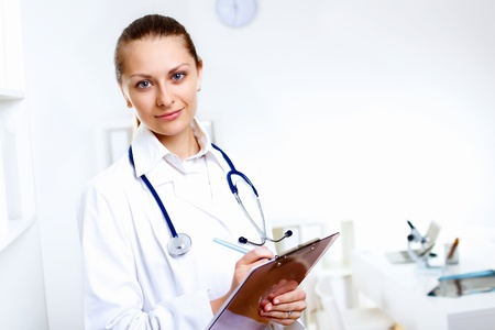 Friendly young female doctor in uniform in medical office photo