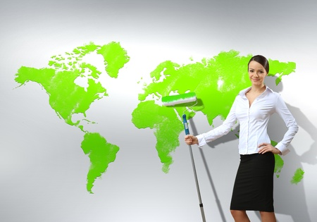 Businesswoman with paint brush and world map on the background photo