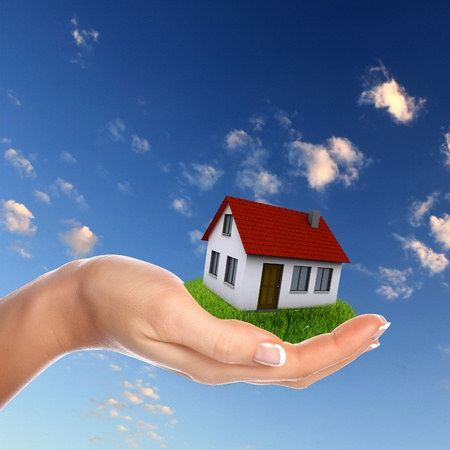 manor: Human hand against blue sky background and house Stock Photo